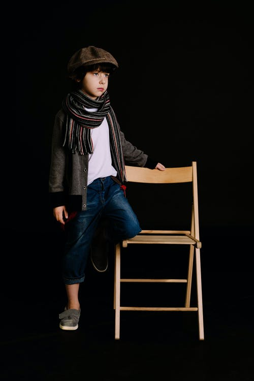 Boy Holding Brown Wooden Chair