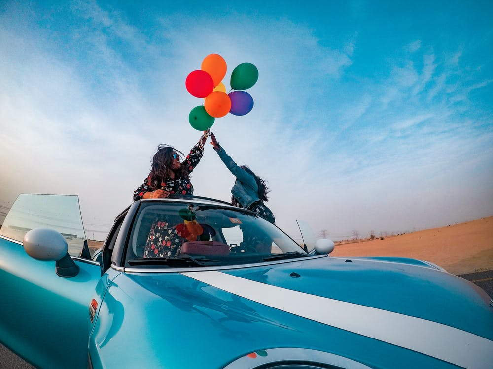 Two Women Holding Assorted-color Balloon Lot