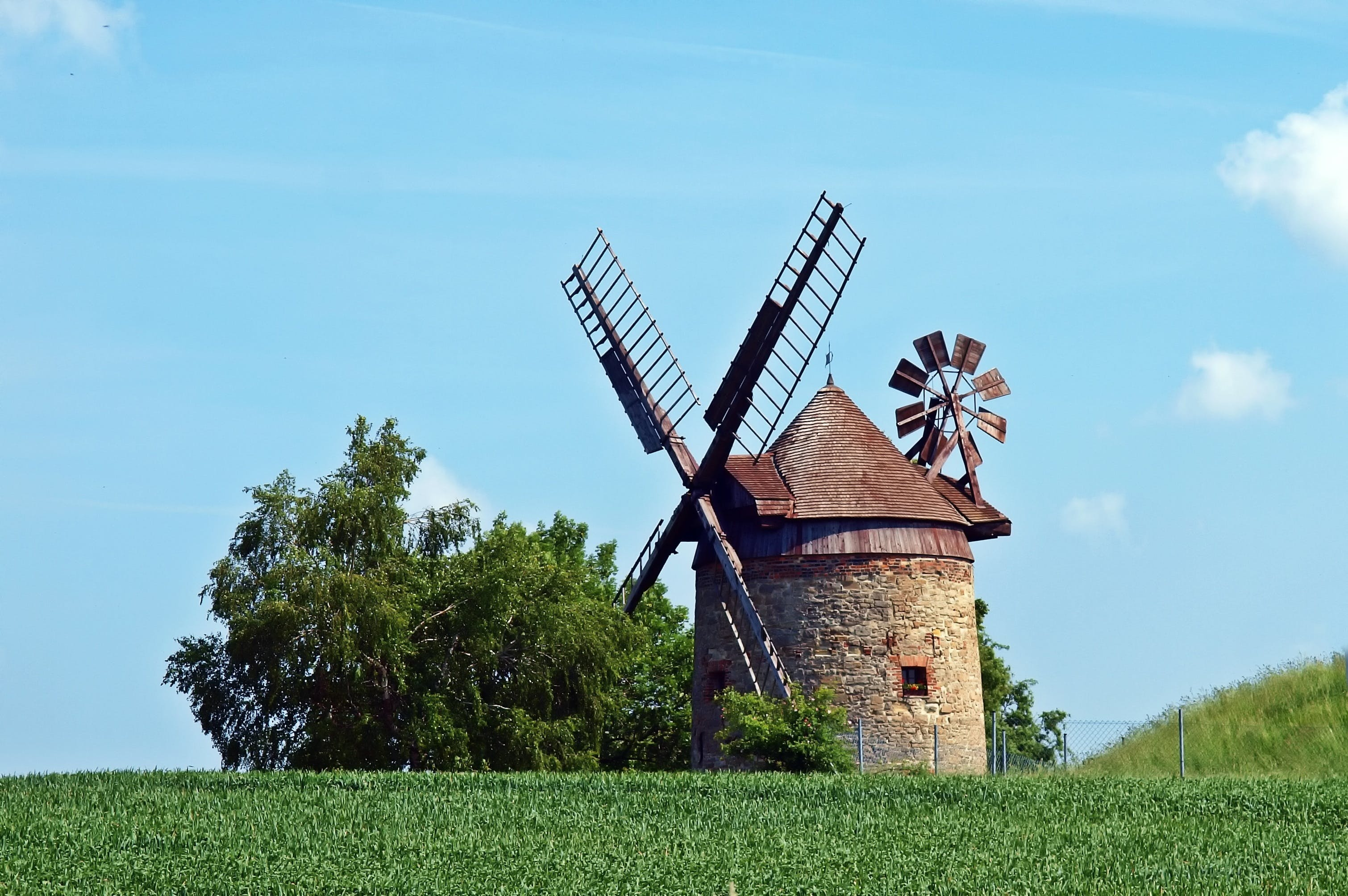 Brown and Gray Windmill Beside Green Tree Under Blue Cloudy Sky during Day Time