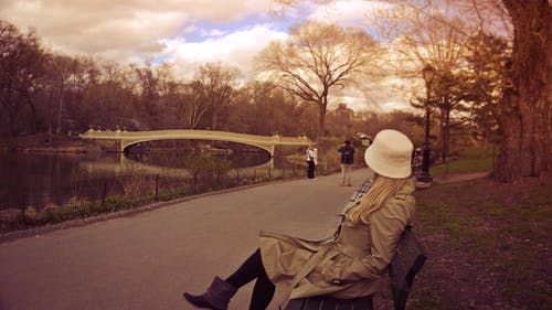 Woman in White Bucket Hat, Brown Coat and Boots Sitting on Bench at Park