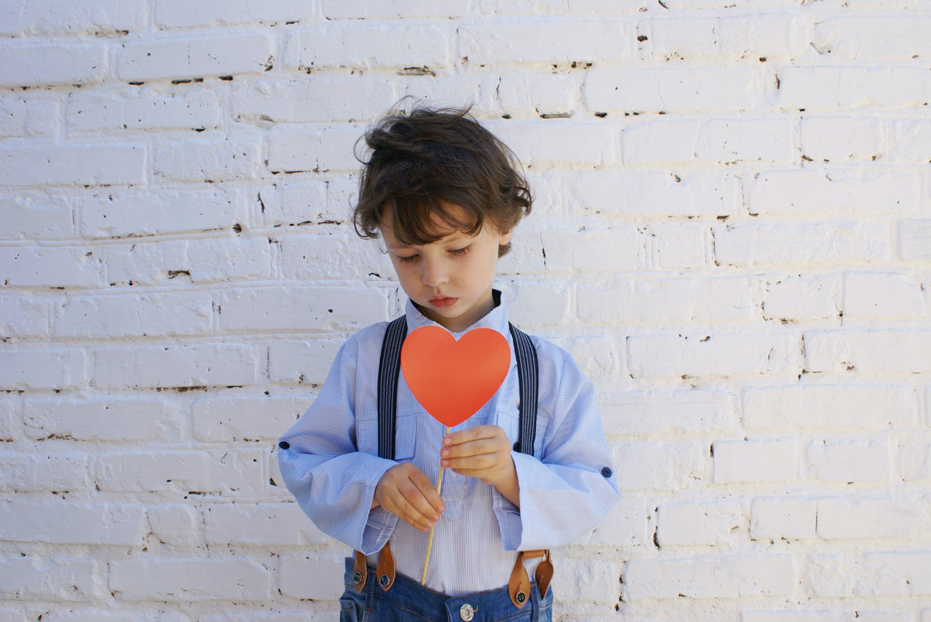 Photo of Boy Holding Heart-shape Paper on Stick