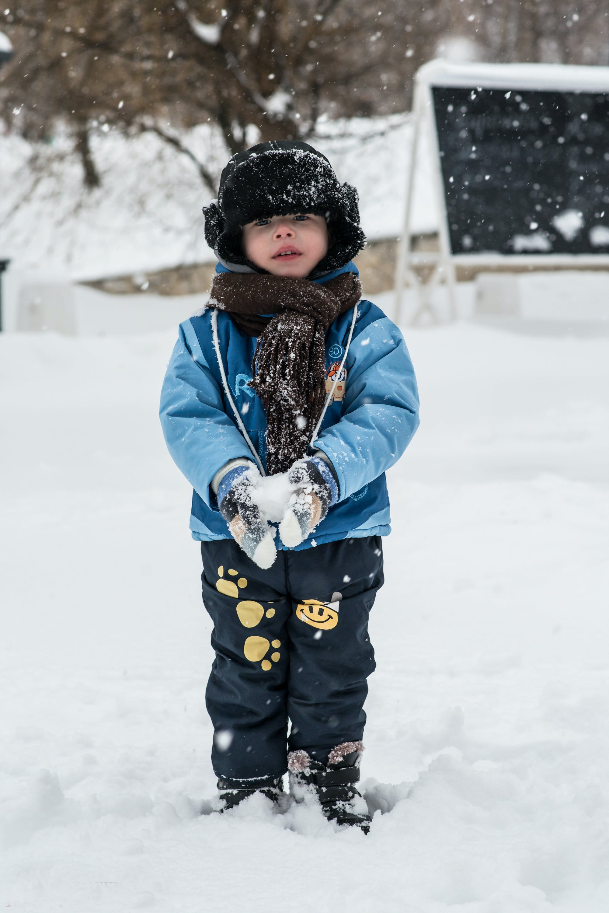 Toddler Standing On Snow Holding Snowball
