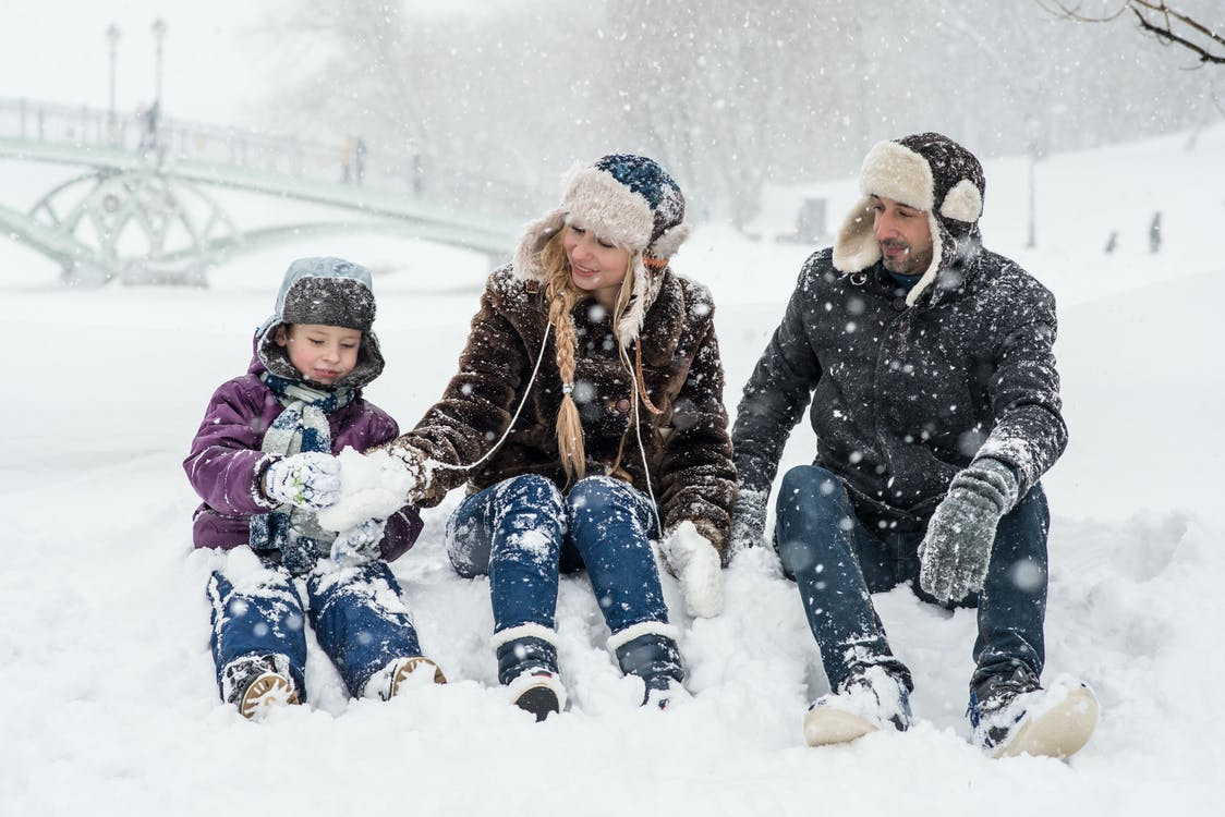 Woman, Man and Girl Sitting on Snow