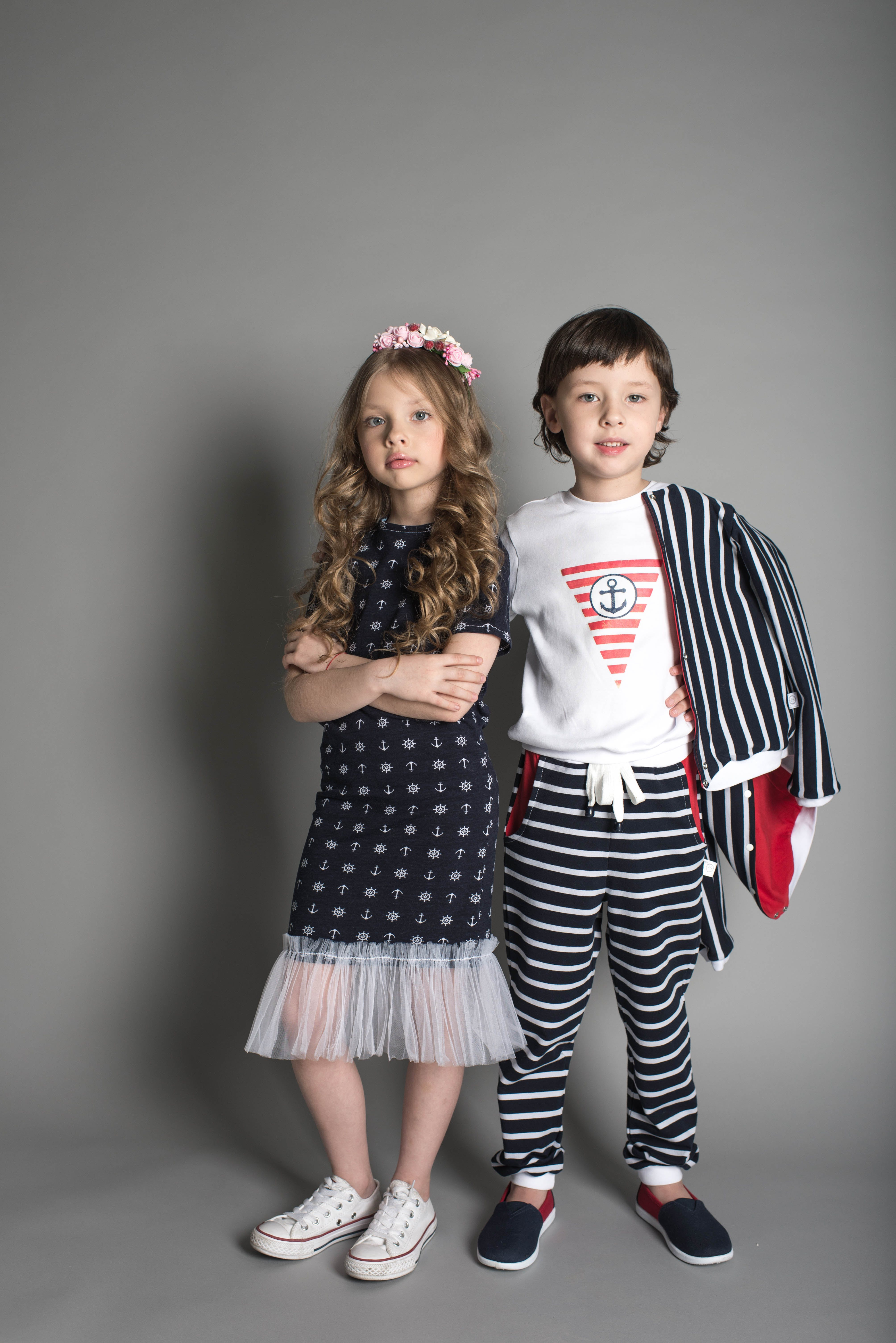 Boy and Girl Standing in Studio In Front of Grey Background