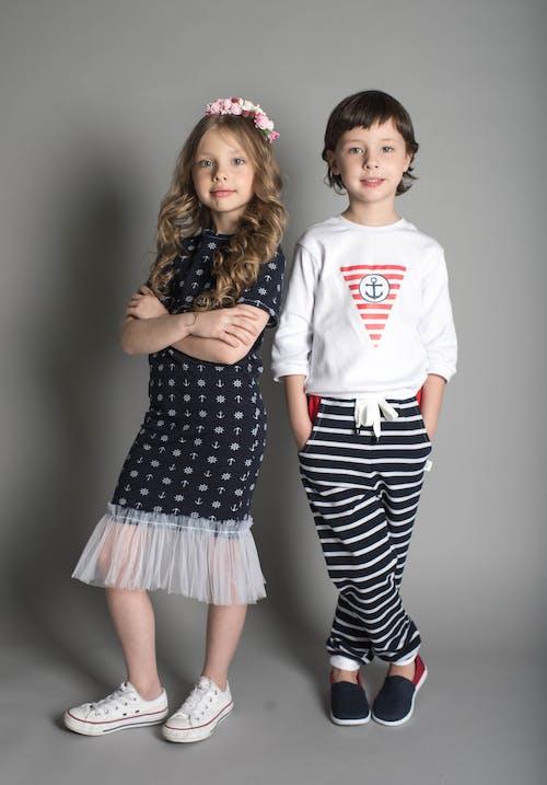 Girl in Black Dress Standing Beside Girl in White Sweatshirt and Black Striped Pants