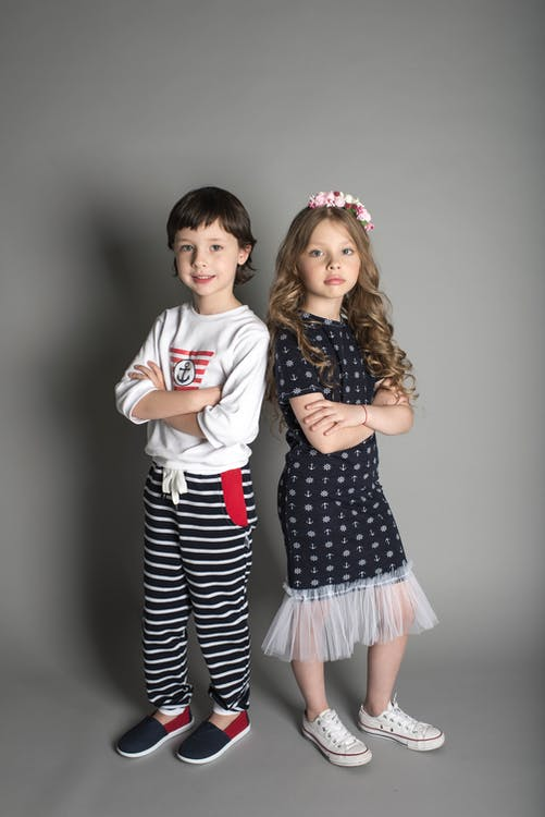Two Children Standing While Crossing Their Arms