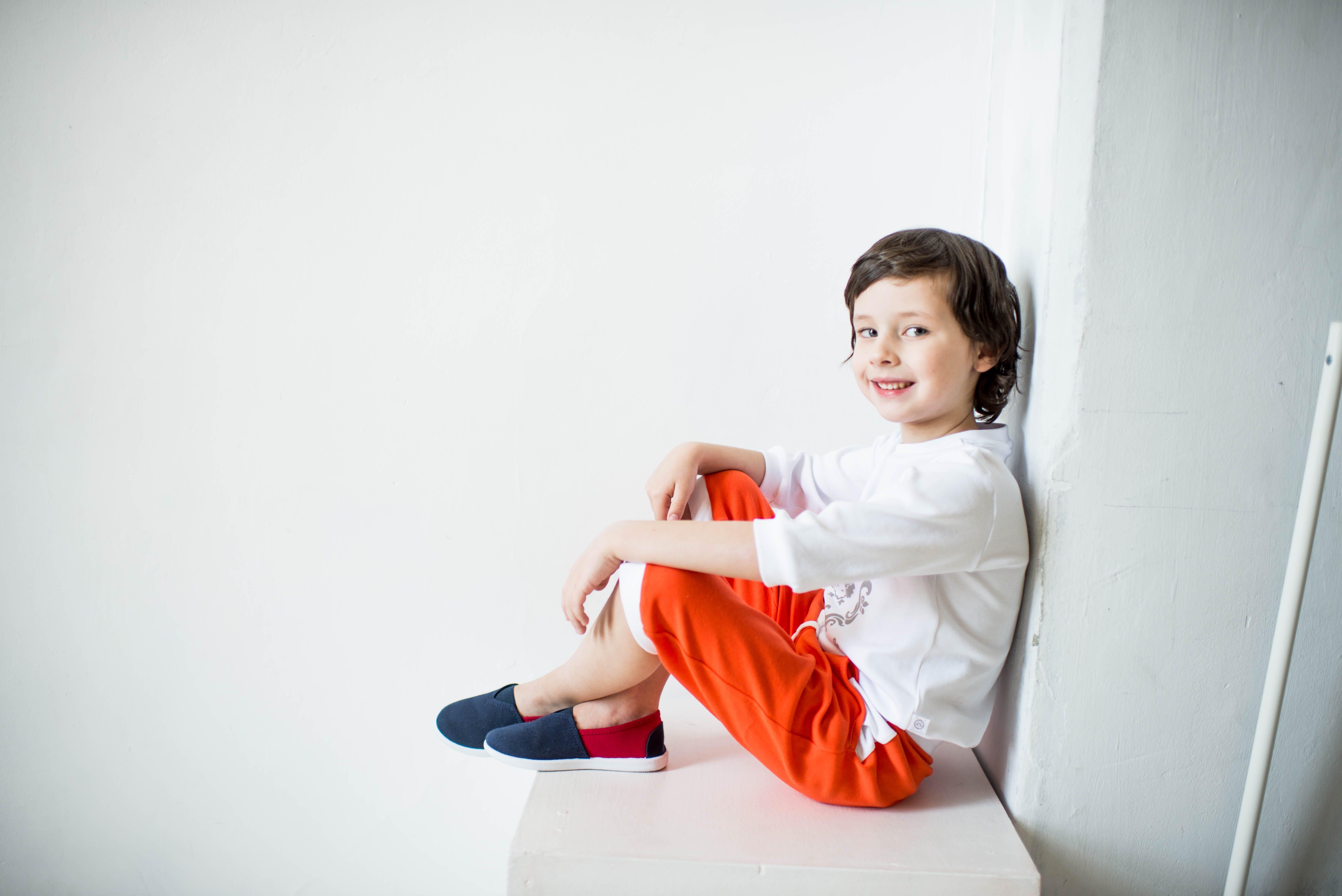 Smiling Boy Wearing White Shirt Leaning on Wall