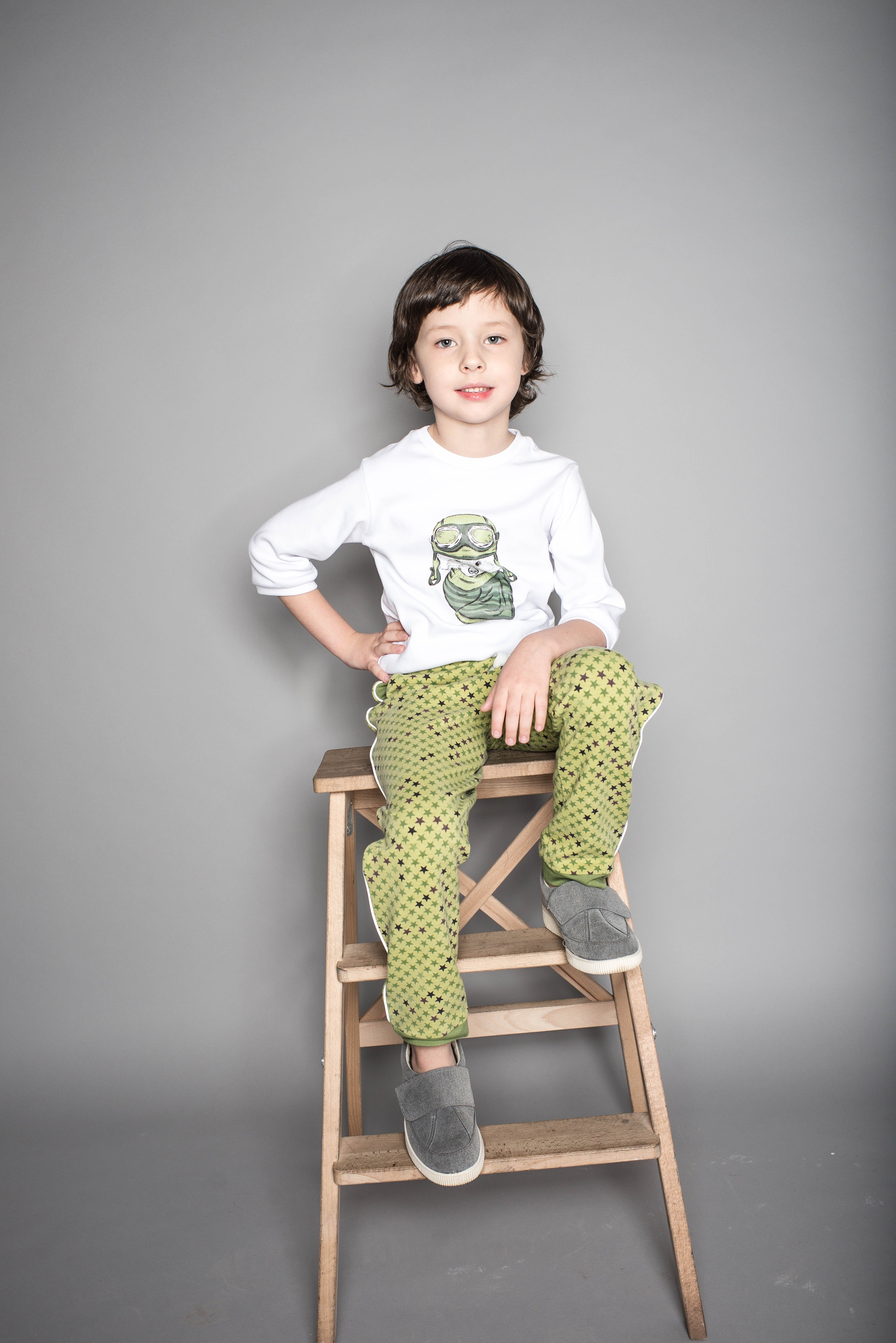 Boy Sitting on Beige Wooden Step Stool