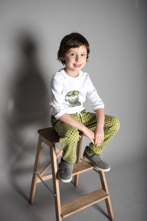 Boy Sitting on Brown Wooden A-frame Steps