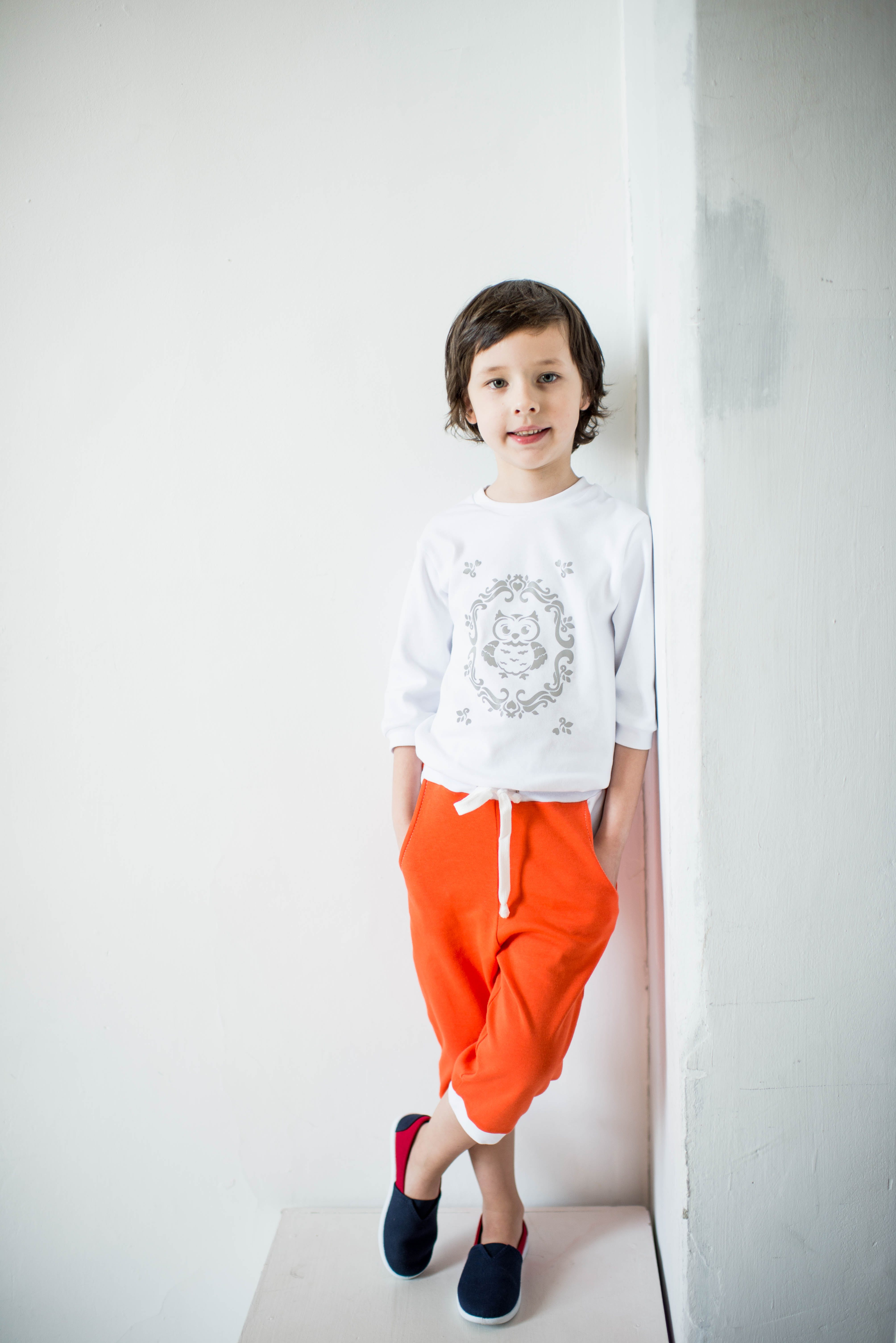 Photo of Child Leaning on Wall With Feet Crossed