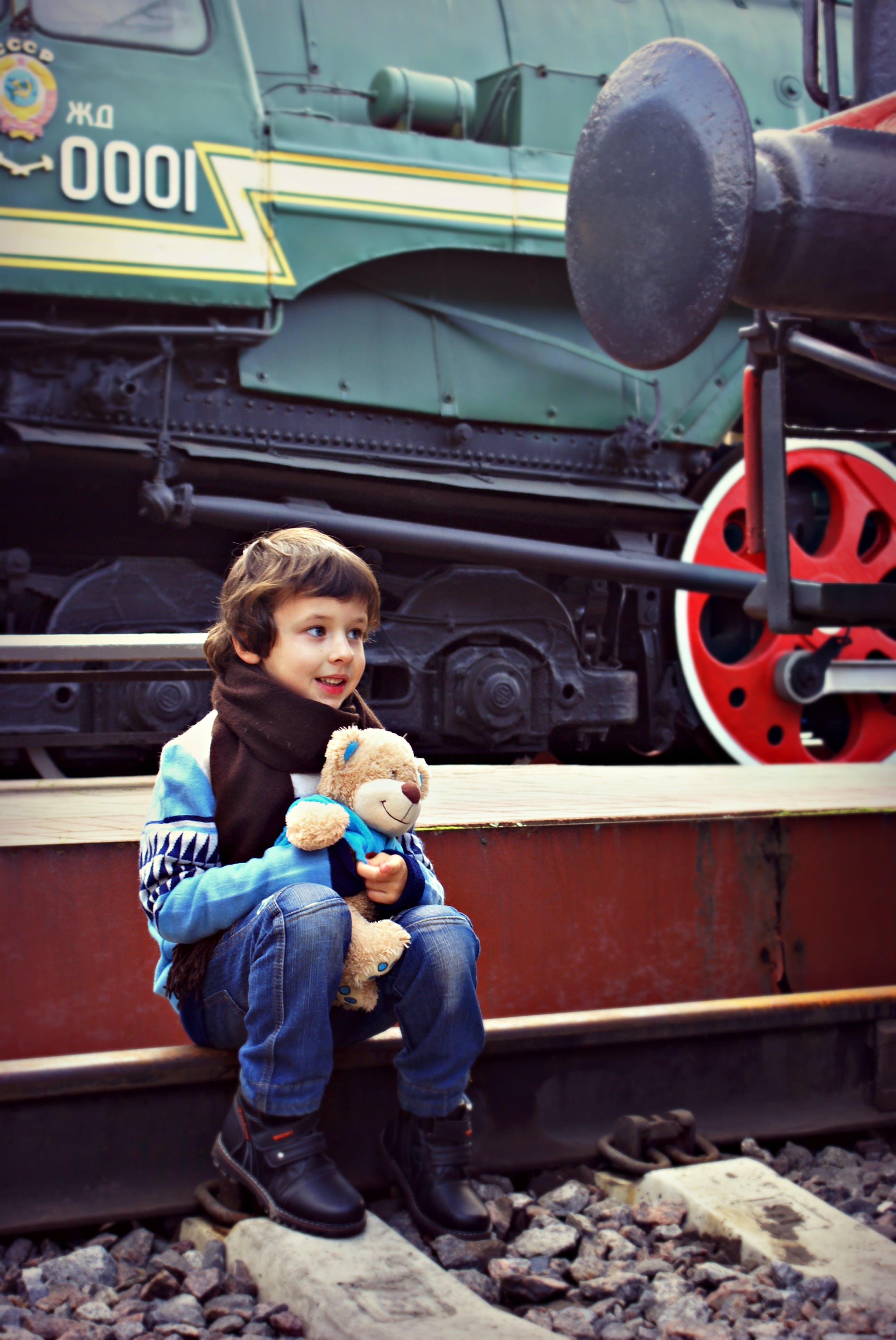 Boy Sitting Near Train While Holding Bear Plush Toy