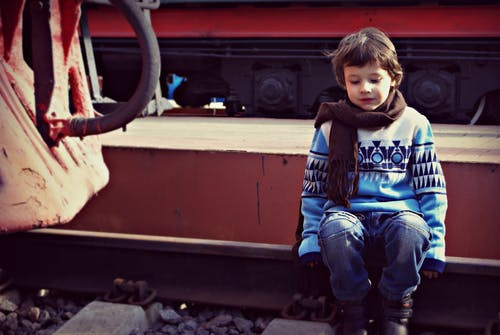 Boy Sitting on Train Rail