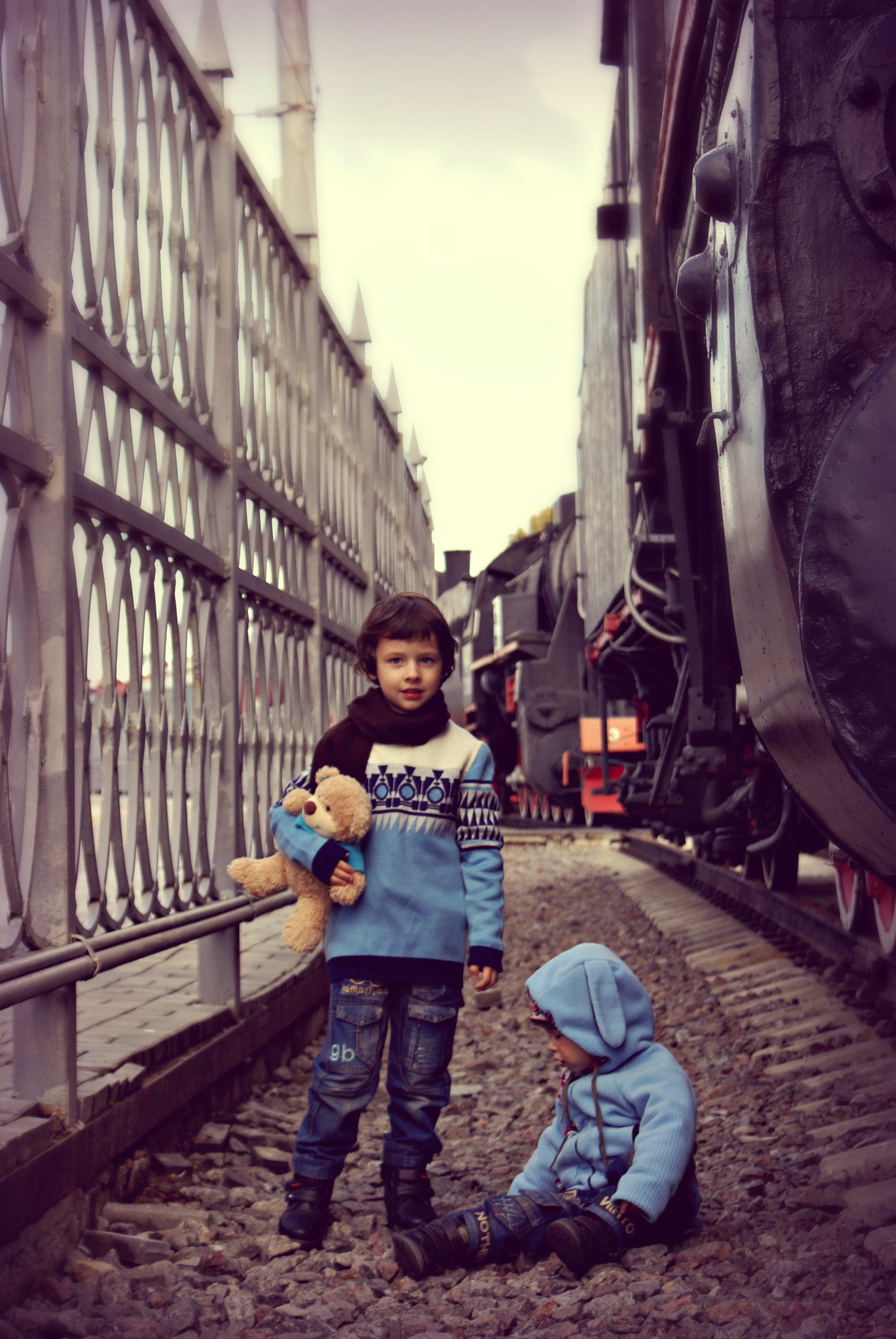 Boy Standing Beside Boy on Ground