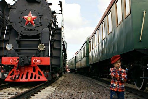 Boy Standing In Between Big Trains