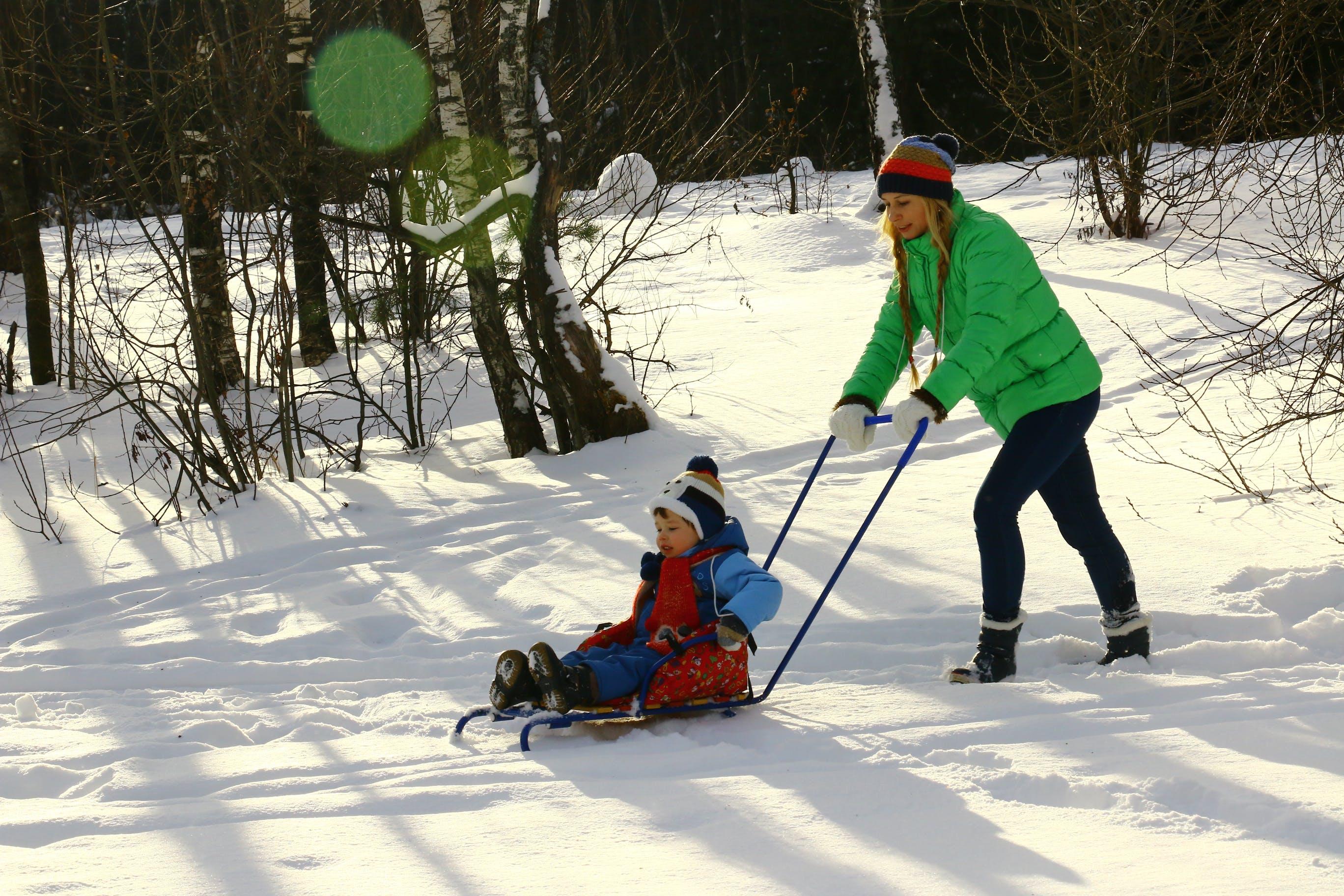 Woman Pushing Toddler on Sled