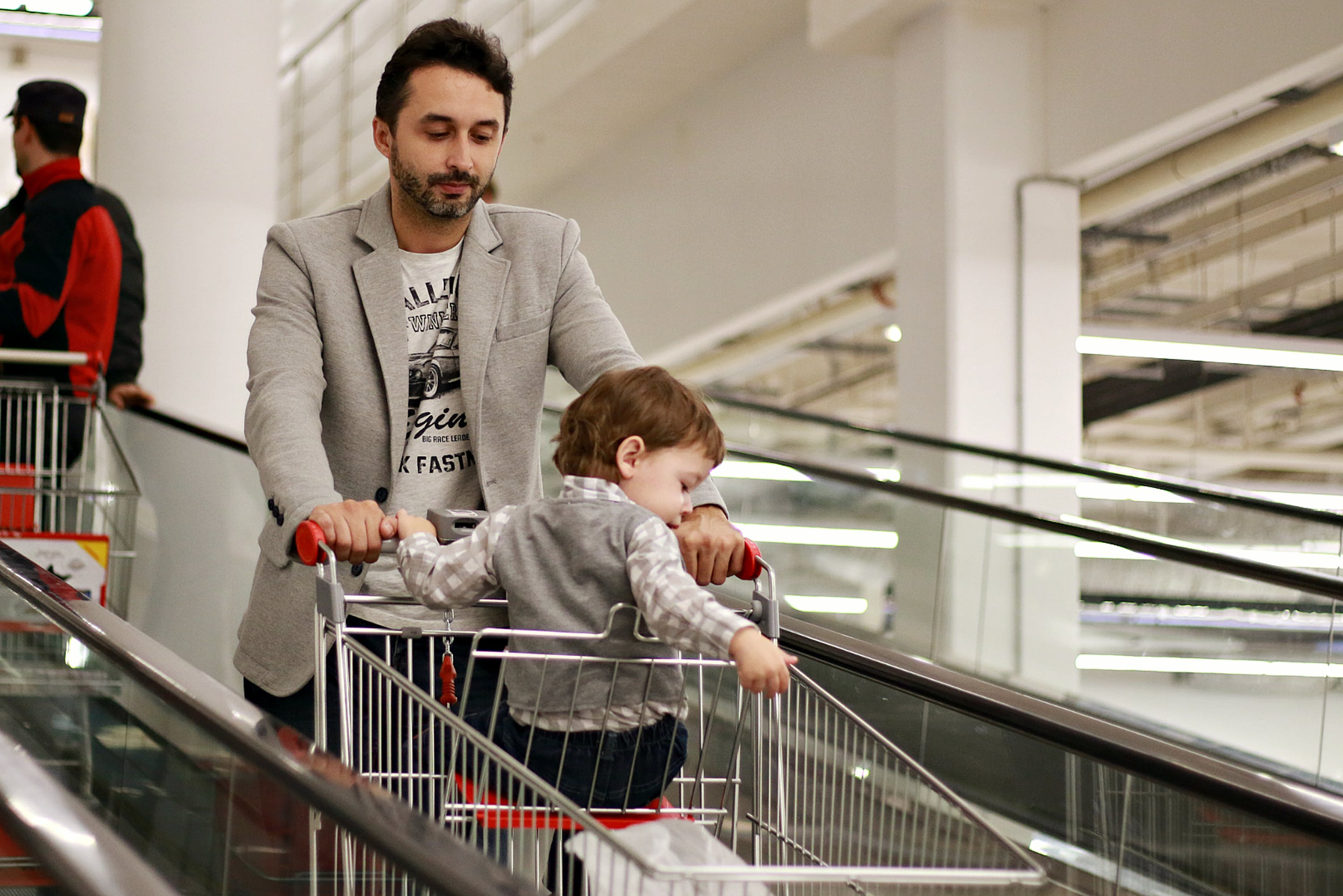 Man Pushing Shoppers Cart With Baby Sitting Inside