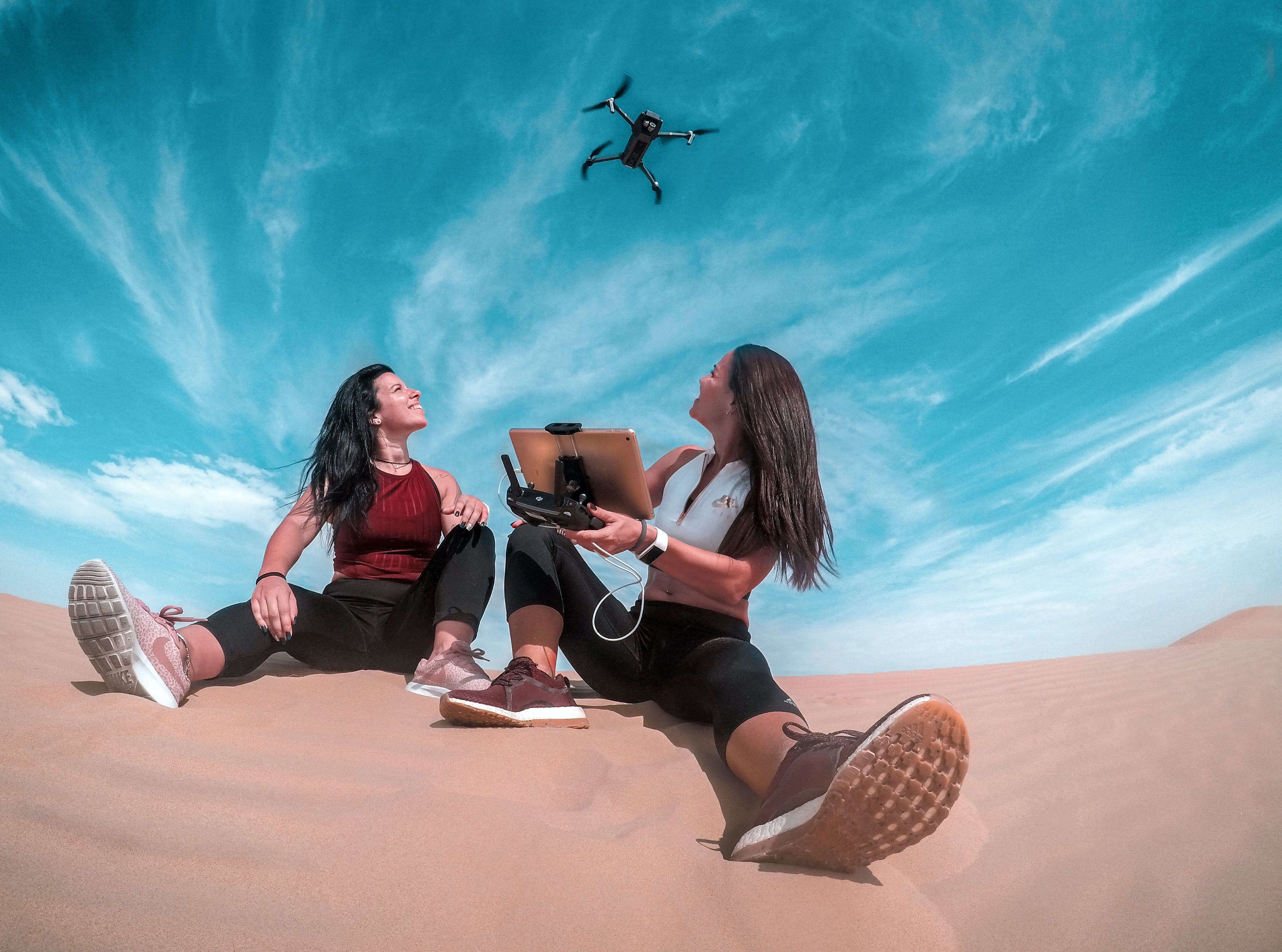 Two Woman Sitting On Sand While Playing Drone