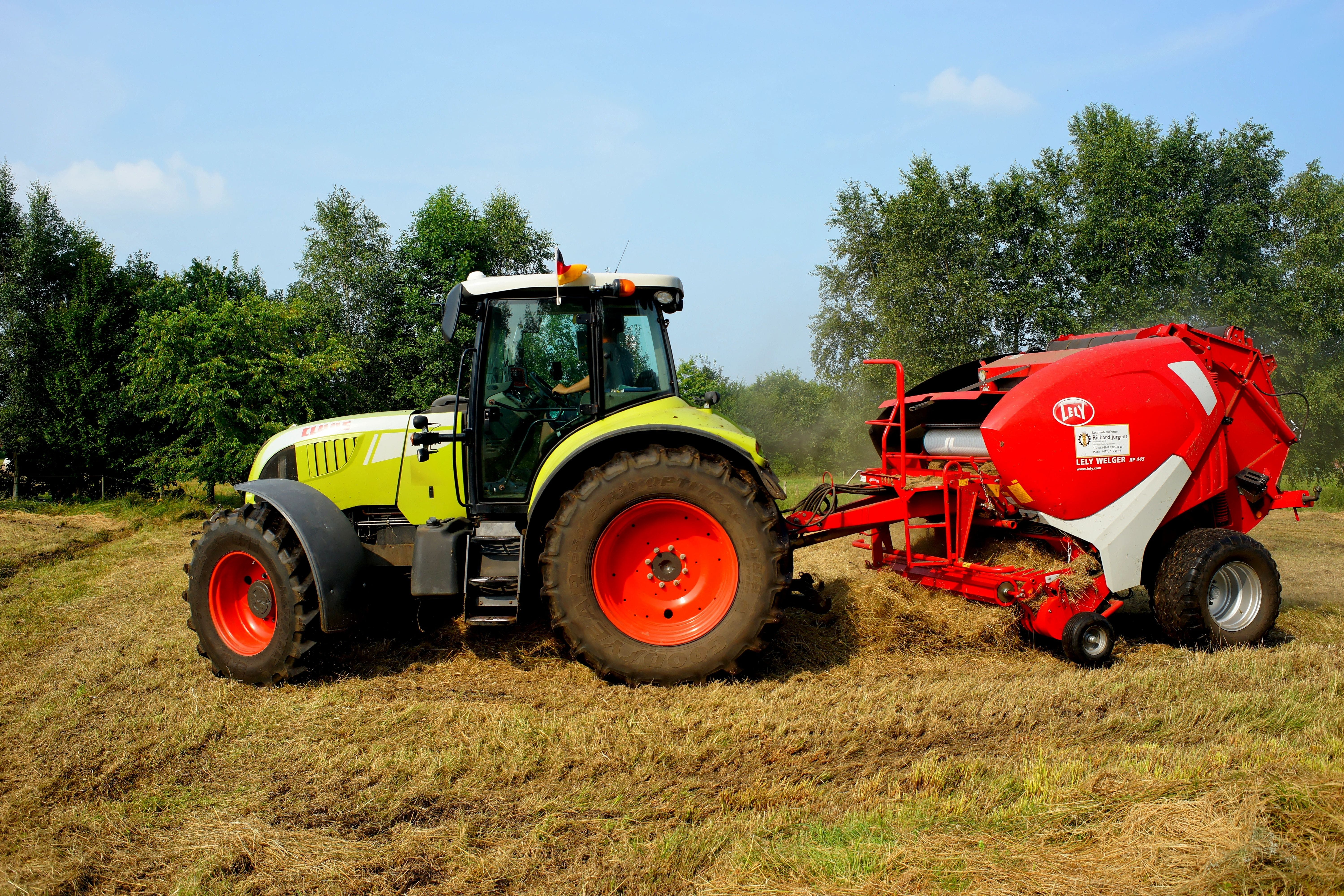 Red Yellow and White Tractor on Grass Field during Daytime