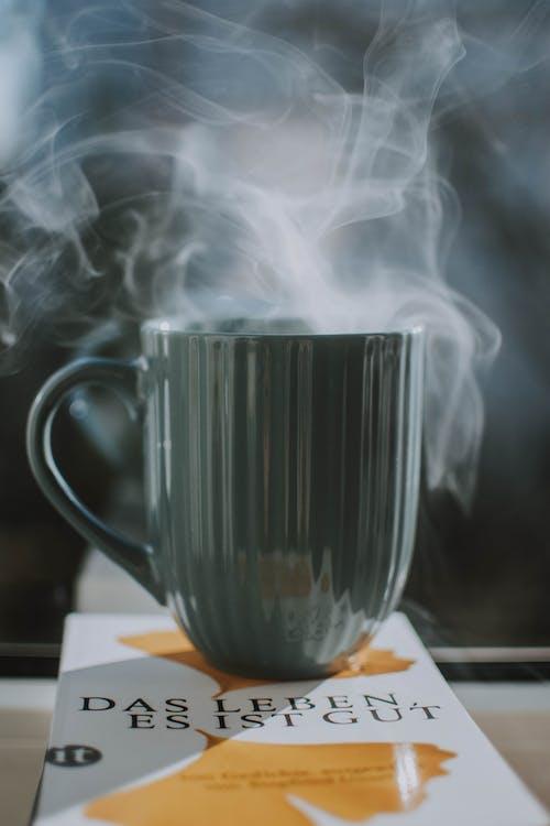 Gray Ceramic Mug on top of  Book