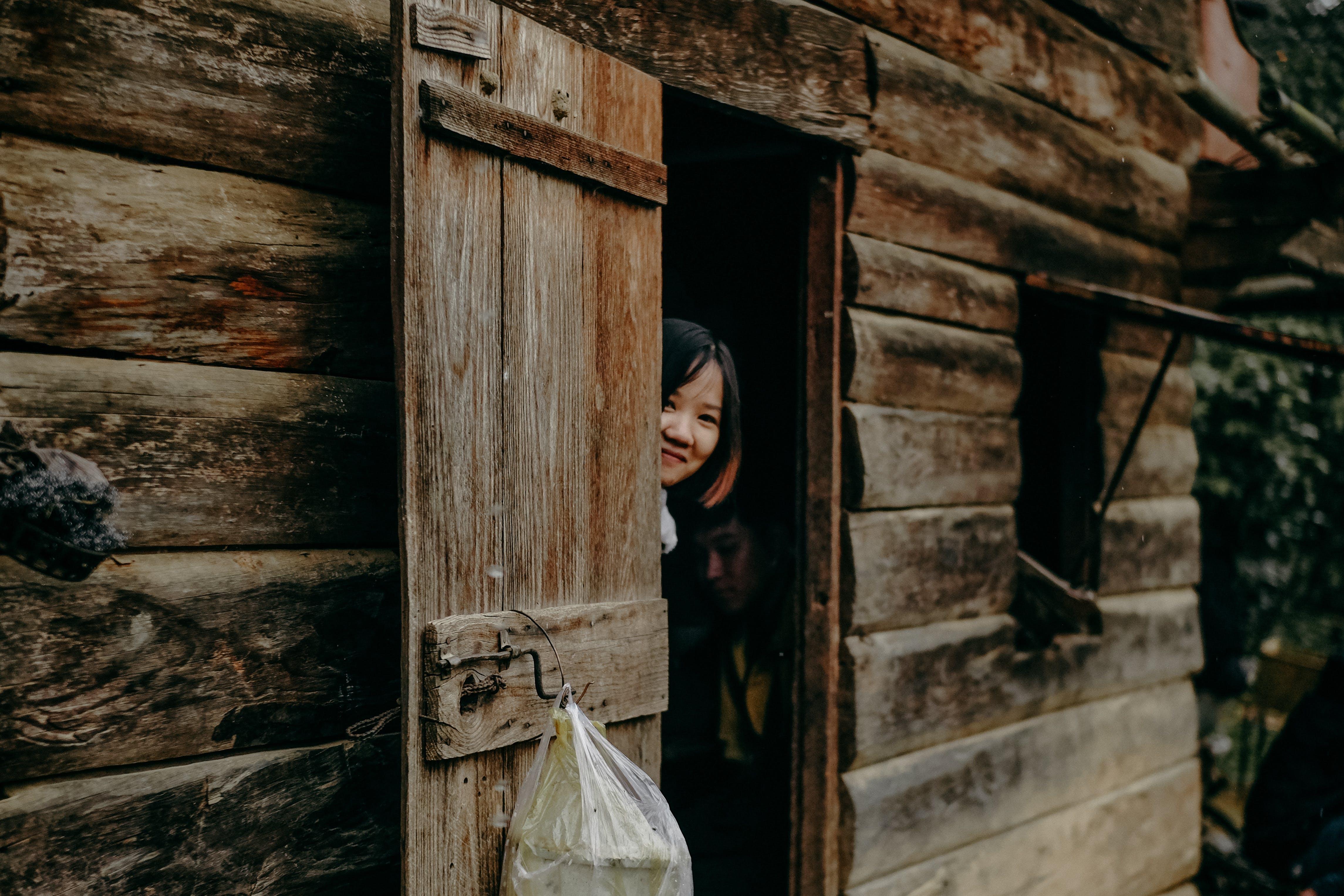 Woman Hiding Behind Cabin Door