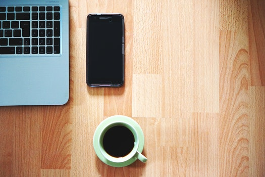 White Ceramic Mug Near Black Smartphone