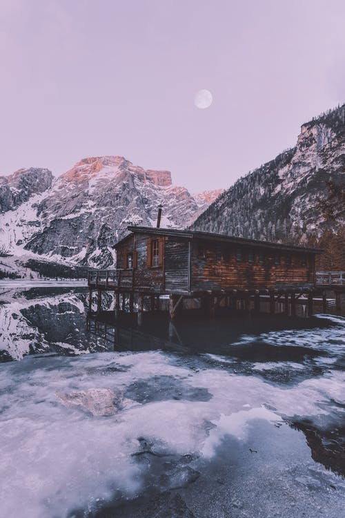 Brown Wooden House Near Snow Covered Mountain