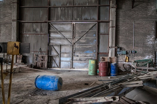 Blue Plastic Barrel on Floor Surrounded by Metal Pipe Inside Warehouse