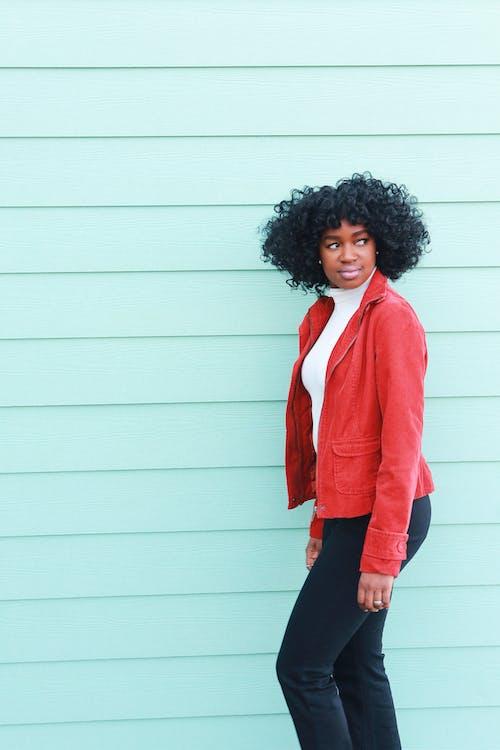 站在淺藍色的牆上,看著斜向一邊的紅色西裝外套的女人