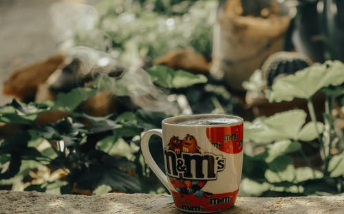 Selective Focus Photo of M&M's Ceramic Mug on Gray Concrete