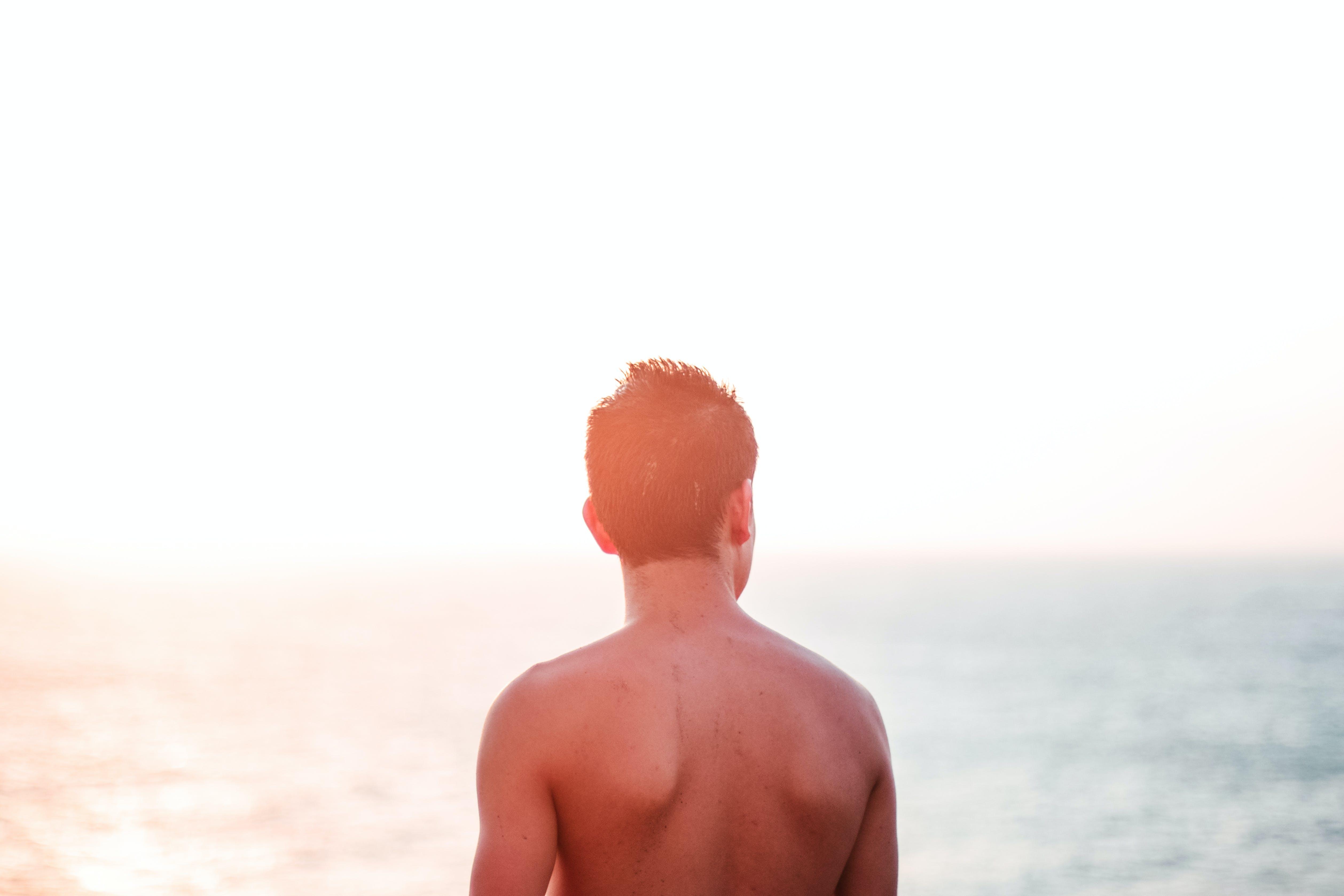 Topless Man Standing At Seashore