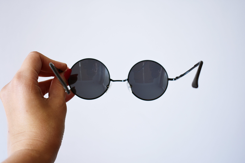 Person Holding Black Framed Sunglasses