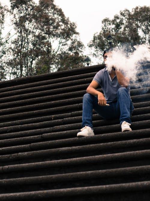 Man Sitting on Stairs Smoking Vaporizer