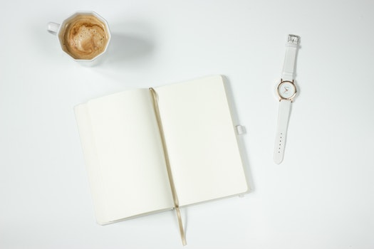 White Leather Strap Silver Round Analog Watch Next to Notebook