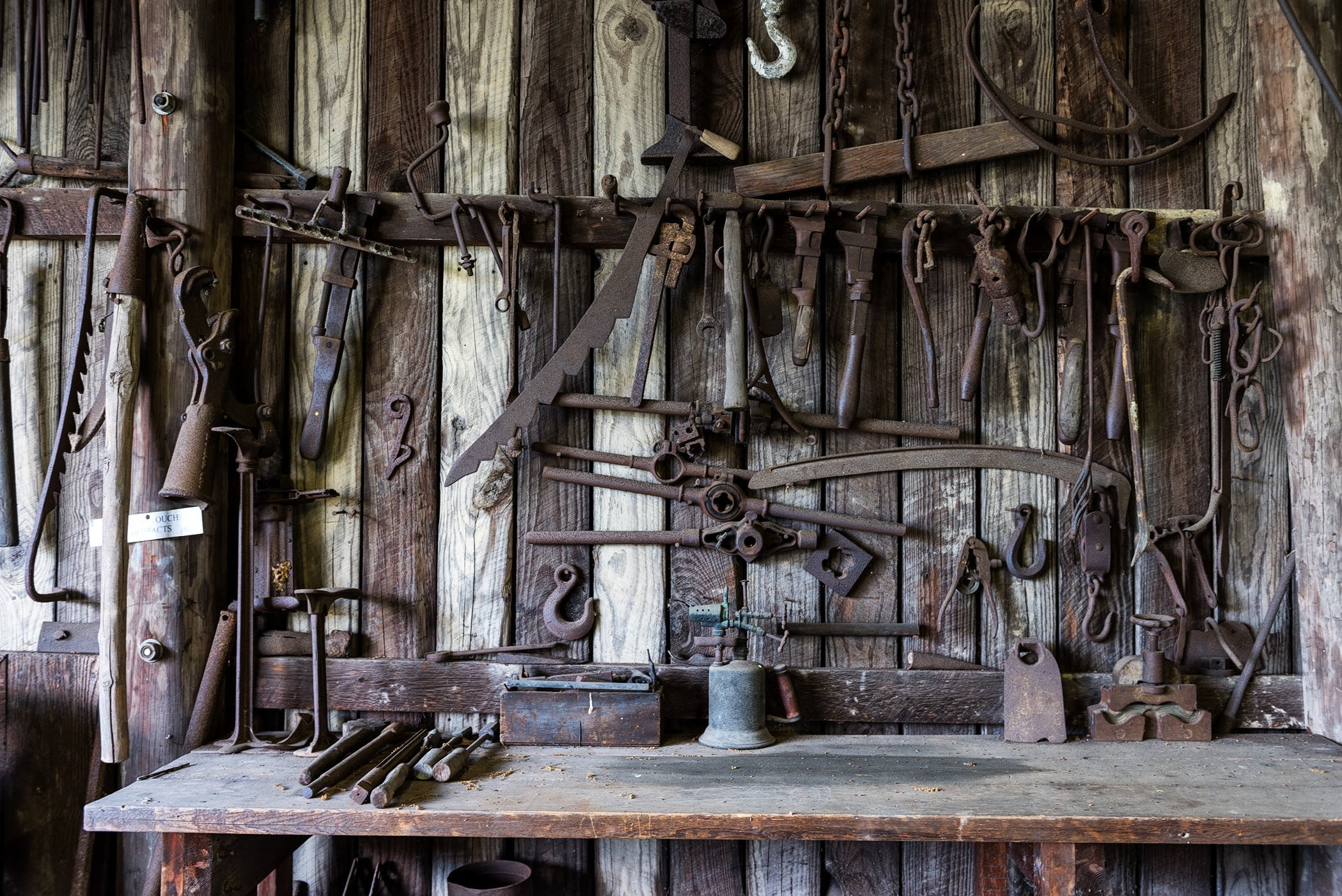 Black Metal Tools Hanged on a Rack Near Table