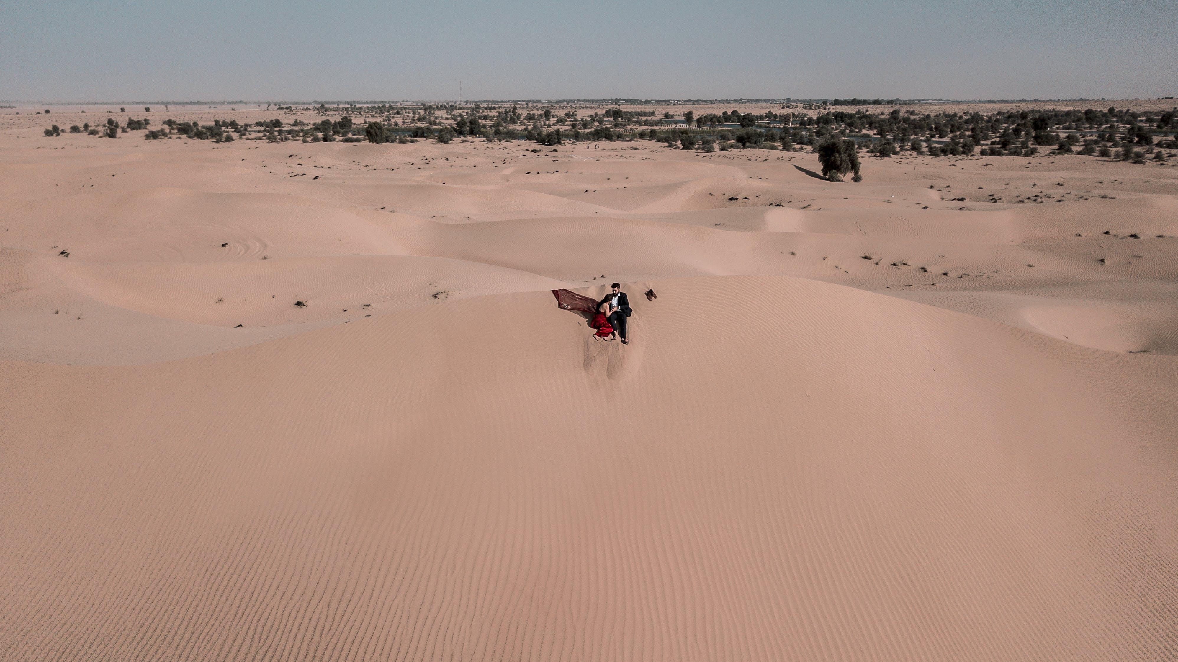 Woman and Man Sitting on Desert
