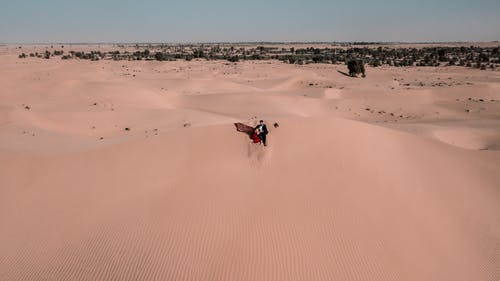 Woman and Man Sitting on Desert