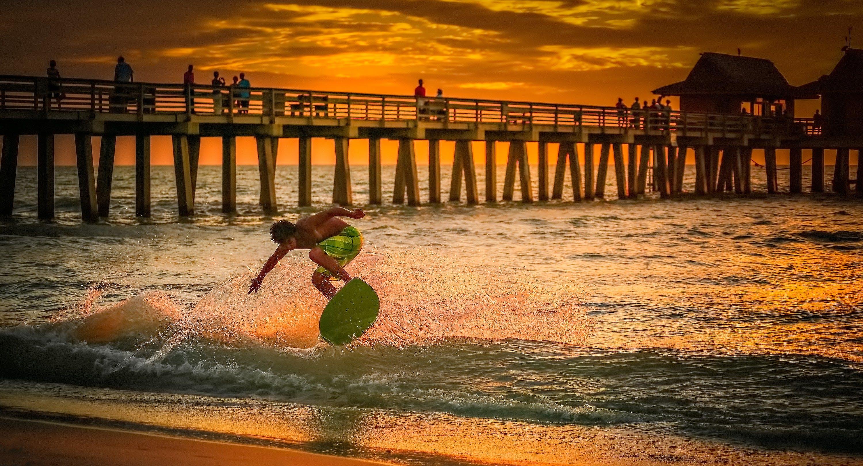 Man Wearing Green Shorts Surfing during Golden Hour