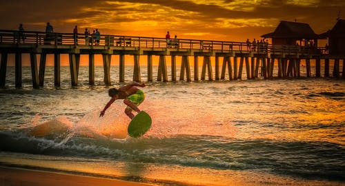 Man Wearing Green Shorts Surfing during Golden Hour