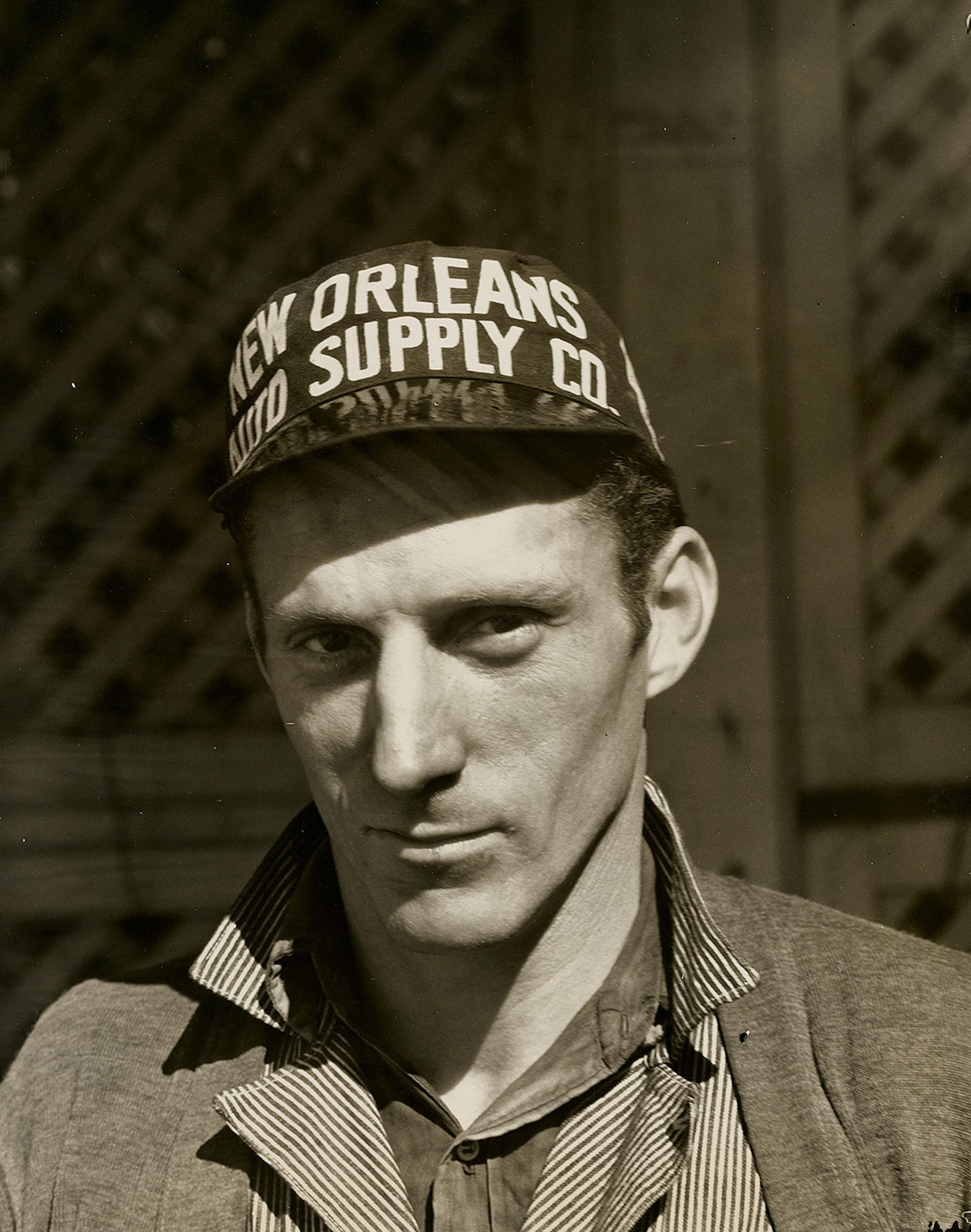 Black and White Photo of Man Wearing New Orleans Supply Hat