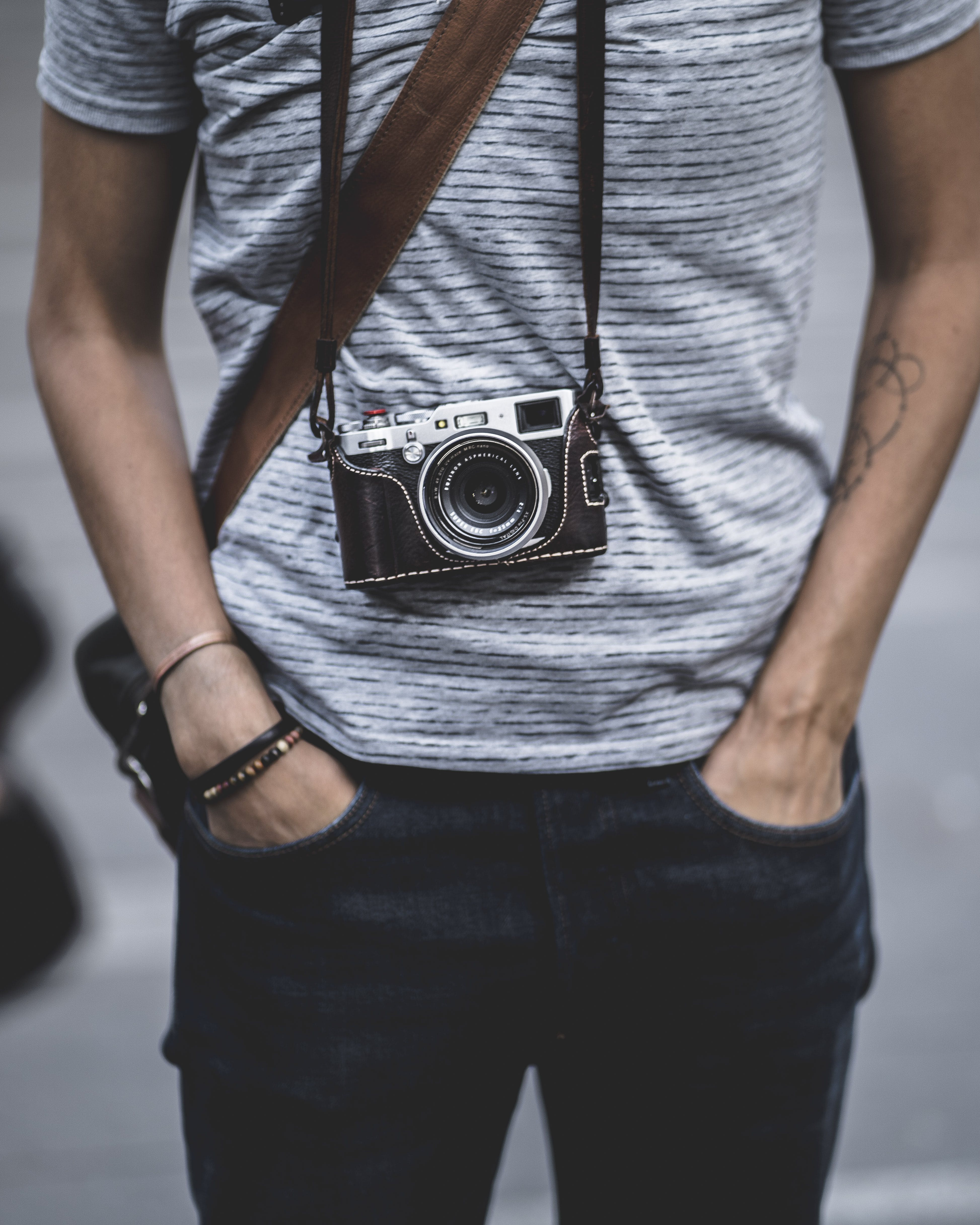 Man Wearing a Camera on his Neck Putting His Hand in Jeans Pocket