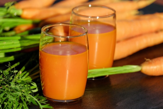 2 Clear Drinking Glass Container with Carrot Juice on Brown Wooden Tabletop in Tilt Shift Lens Photography