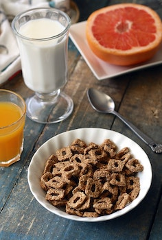 Chocolate Cereal on White Bowl Near Glass of Milk