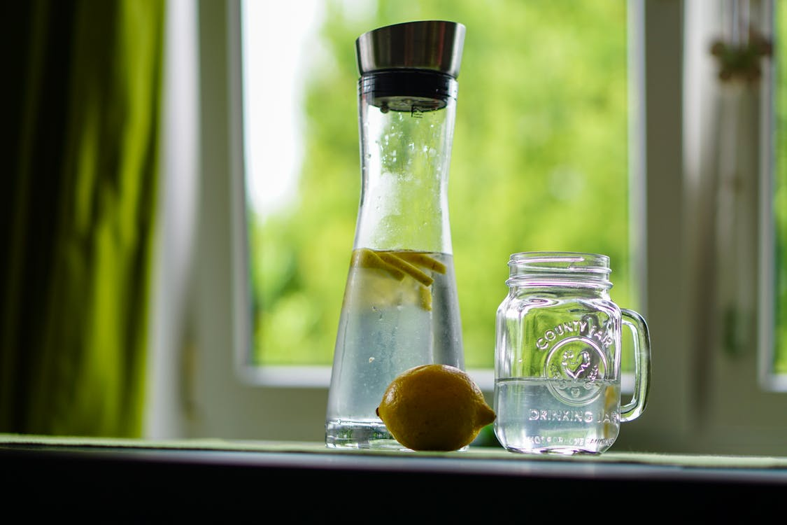 Shallow Focus Photography of Yellow Lemon Near Glass Mason Jar and Glass Decanter