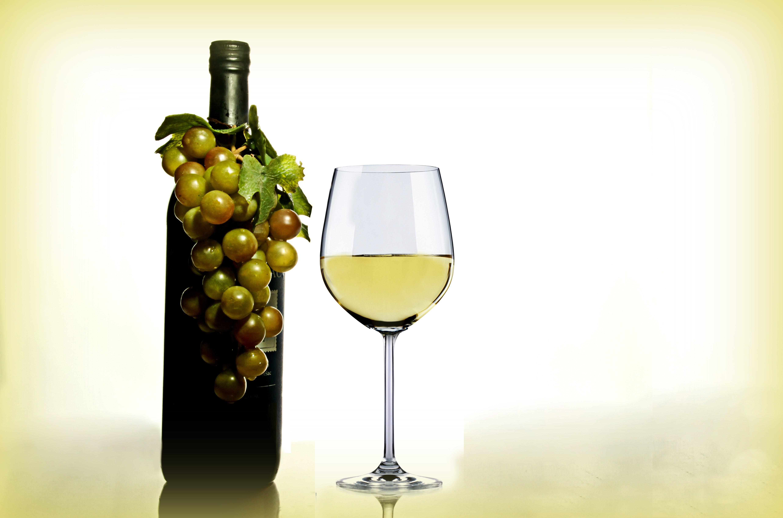 Wine in Wine Glass Near Green Glass Bottle