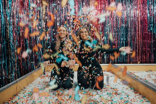 Two Women Kneeling While Throwing Confetti