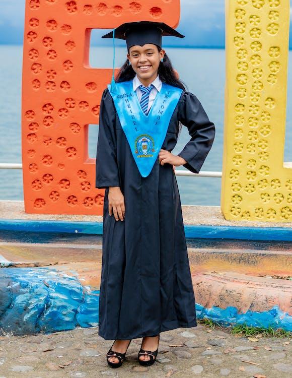 Woman in Academic Dress Standing in Front of Ocean