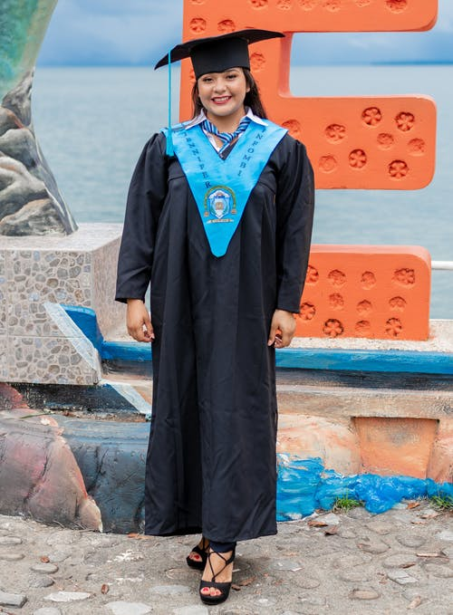 Woman Wearing Blue and Black Academic Dress in Front of Orange Letter E Standee