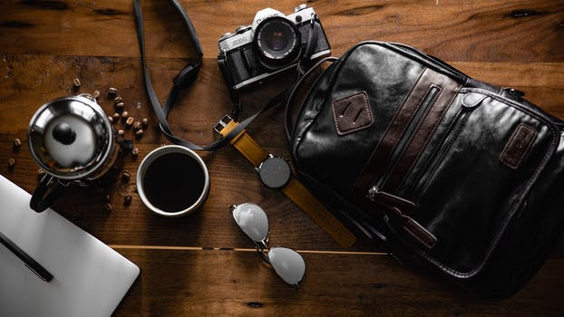 bca894f16596 Flat Inlay Photography of Black Leather Backpack, Camera, Watch and Cup of  Coffee