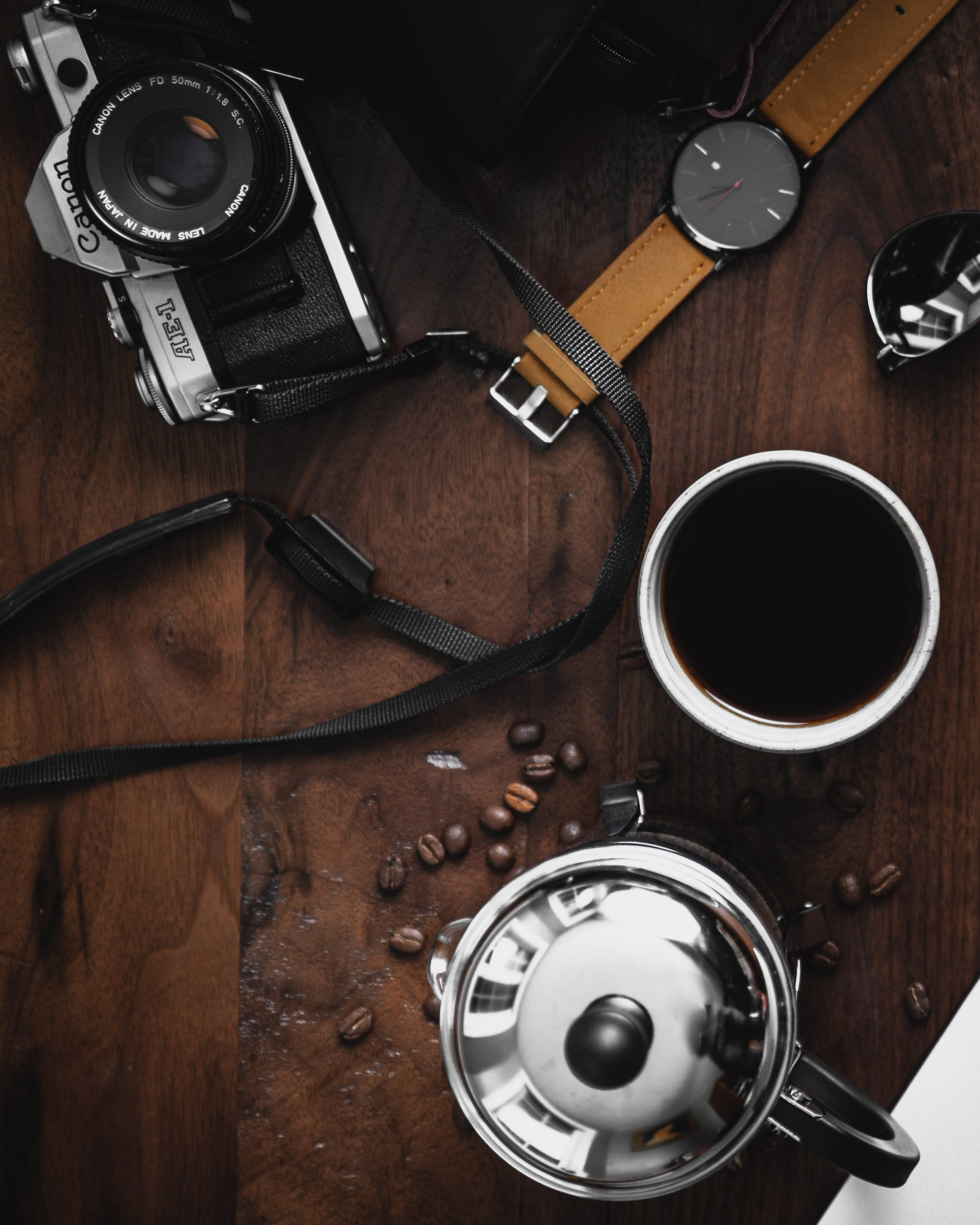 Flat Lay Photography of a Camera, Coffee Mug and Wristwatch