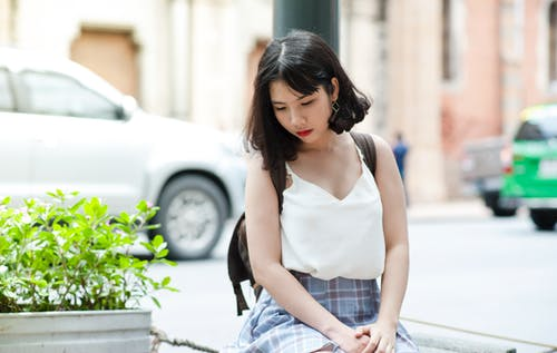 Photo of Woman Sitting Near Plants